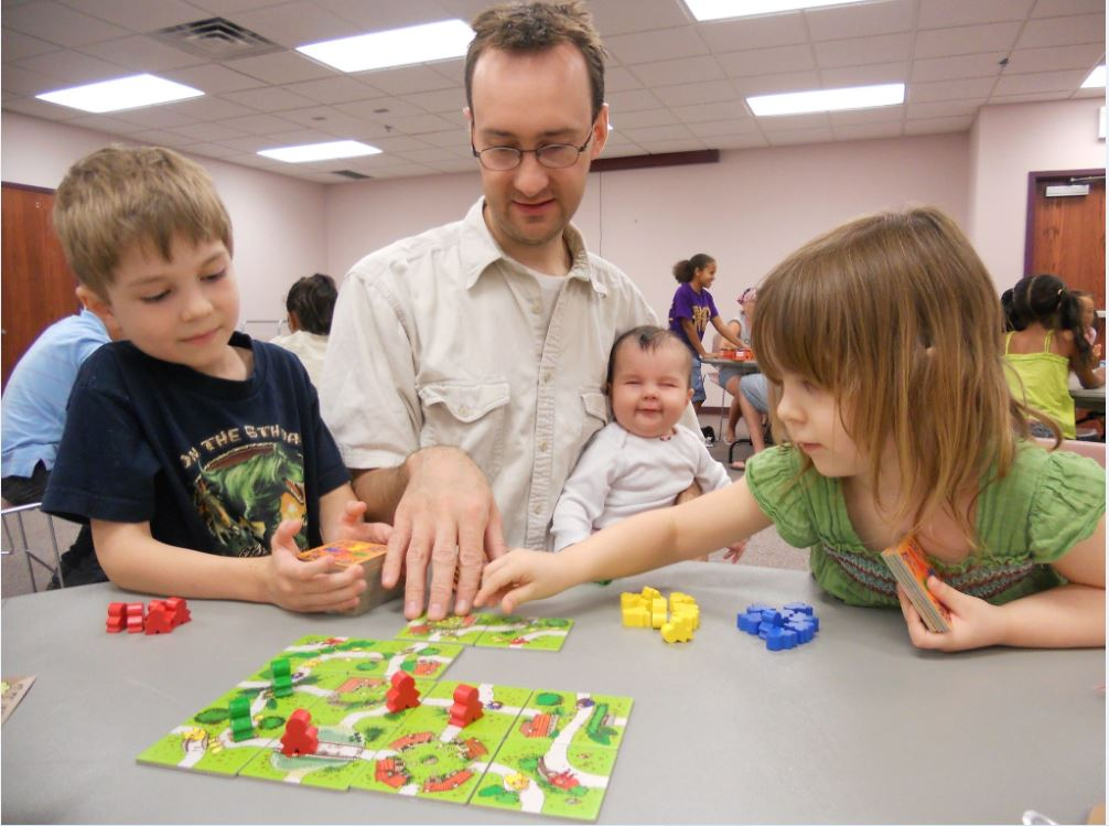 father participates indoor activities and educating with children